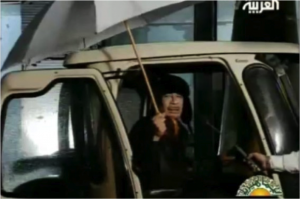 Een apetrotse Kadhafi poseert met paraplu op de Libische staatszender.